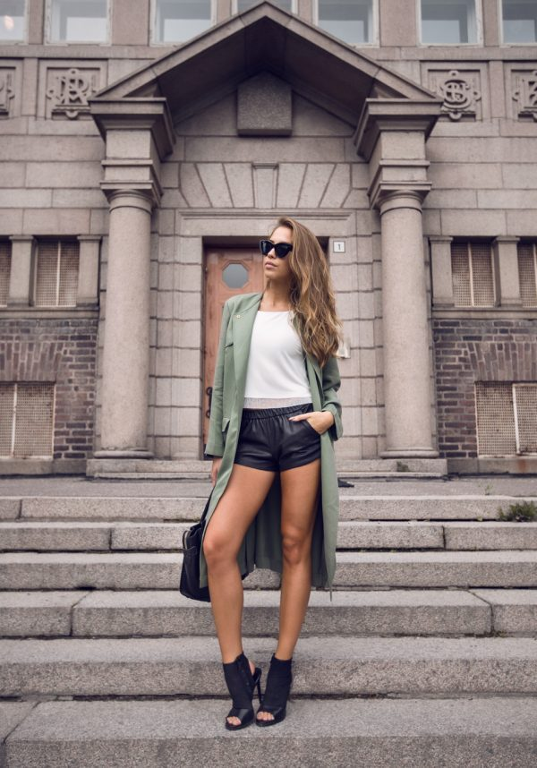Kenza Zouiten is switching it up in this funky and alternative teal green trench, matched with cute leather mini shorts and a pair of classic sunnies. We love that this look is a new and authentic way to wear the trend. Trench Coat: Ivy Revel, Shoes/Top/Shorts: Zara, Bag: Celine.