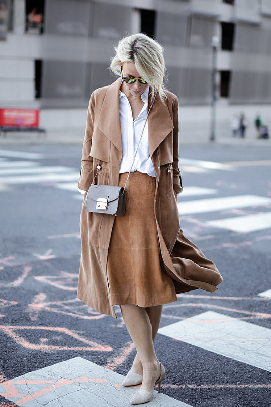 Louise Ebel shows us the versatility of the classic trench coat, wearing an interesting suede trench with a matching midi skirt and a pretty white blouse. We love the retro aesthetic of this look!   Coat: French Connection, Top: Norstrom, Skirt: Ann Taylor, Heels: Vince.