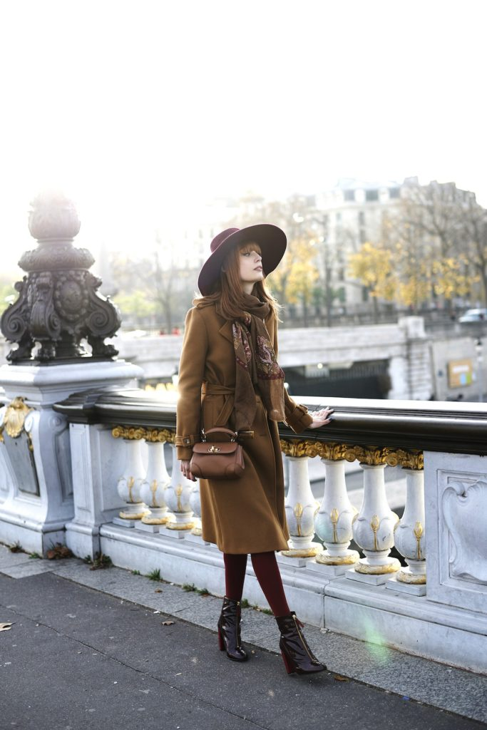 This wonderful trench coat style consists of warming autumnal colours such as burgundy, maroon, and brown. We love Louise Ebel's choice to stray away from classic spring colours and bring the best of autumn back!   Coat: Gérard Darel, Dress: Pablo, Bag: Ralph Lauren, Hat: Tand3m, Boots: Kurt Geiger.