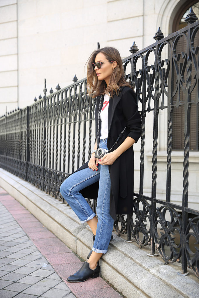 A minimalistic black trench coat is the perfect finish to a casual jeans and tee outfit like this one worn by Silvia Zamora. Adding elegance and edge to your look, a black trench is a must have!  Trench: Blanco, T-shirt/Jeans: Levi's, Boots: Senso.