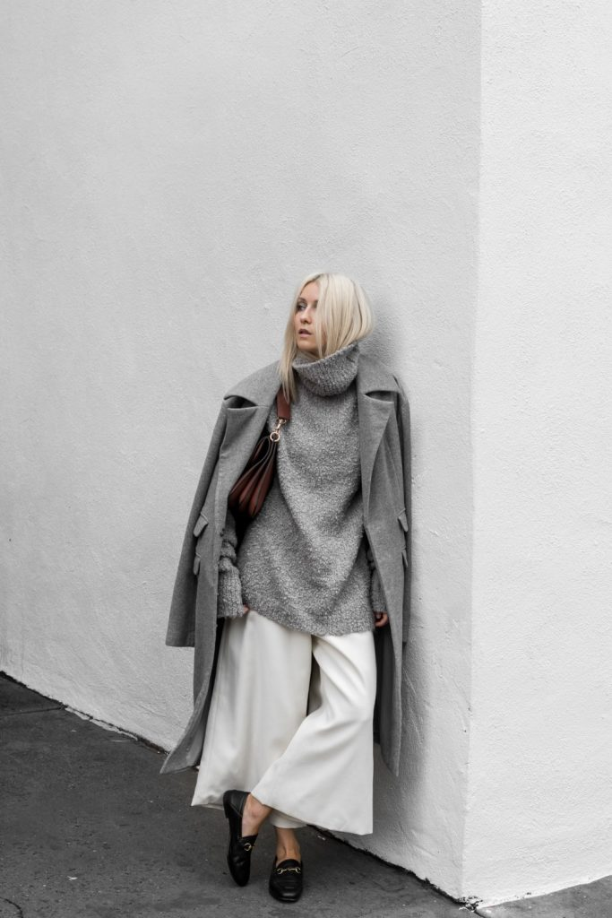 Loafers are the perfect match to this outfit, styled by Figtny, which consists of an oversized polo neck jumper, wide legged white culottes, and a military style overcoat to give that androgynous feel.   Coat,Loafers: Net-A-Porter, Trousers: Matchesfashion.