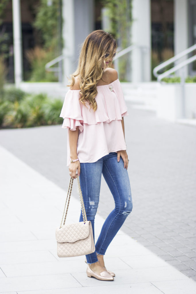 Wearing an off the shoulder top is the perfect way to capture your femininity. Brenna pairs this gorgeous pink layered piece with distressed denim jeans and a pair of loafers for a casual but sexy street style. Top: Lulu's 'Born To Wander', Jeans: Dittos.