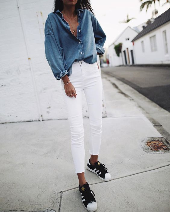 Andy is wearing skinny white jeans with an oversized 'boyfriend' fit denim shirt, open at the neck, paired with simplistic gold jewellery and monochrome Adidas sneakers.   Shirt/Jeans: Topshop, Sneakers: Adidas.