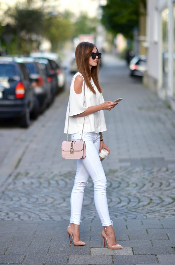 Barbora Ondrackova is rocking this striking style consisting of white jeans, a shoulderless top with bell sleeve detailing, and a pair of nude heels to match nude accessories.   Blouse: Topshop, Jeans: Mango, Heels: Christian Louboutin, Bag: Valentino.