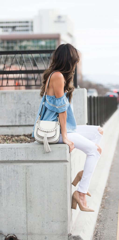 Wearing distressed white jeans with a shoulder-less denim top, Christine Andrew has created the perfect spring/summer look. She wears this style with suede nude heels and a white cross body bag.   Top/Jeans: Bloomingdale's, Heels: Intermix.