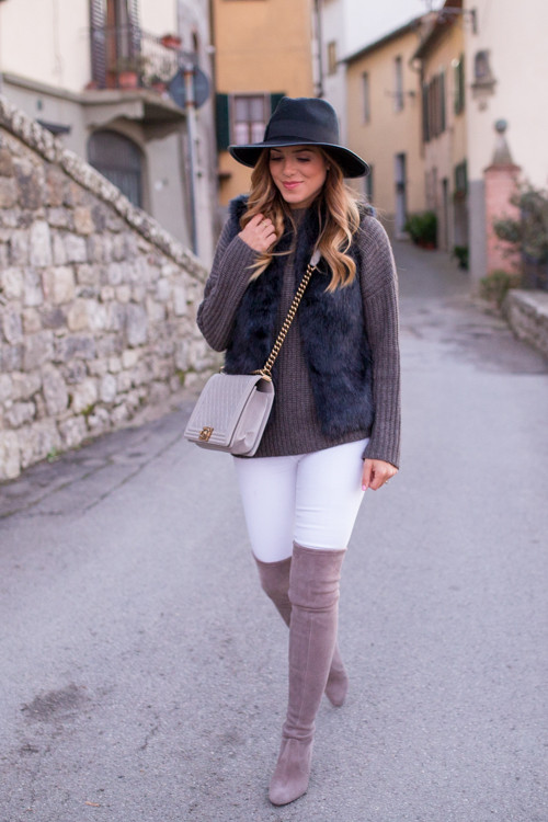 Julia Engel shows us that white jeans needn't always be a solely summer style, pairing these skinnies with a beautiful faux fur vest and a classic knitted sweater in a warming shade of brown.   Jeans: Frame Denim, Boots: Stuart Weitzman.