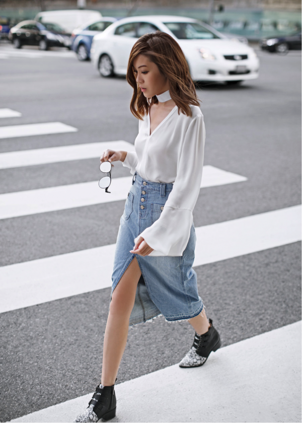Jenny Tsang puts a contemporary twist on a classic look; the denim skirt with its frayed edges create grungy vibes, and teamed with the flared white shirt and bold black boots, a bold look is created. Shirt: Saks Fifth Avenue, Skirt: Nordstrom, Boots: Revolve