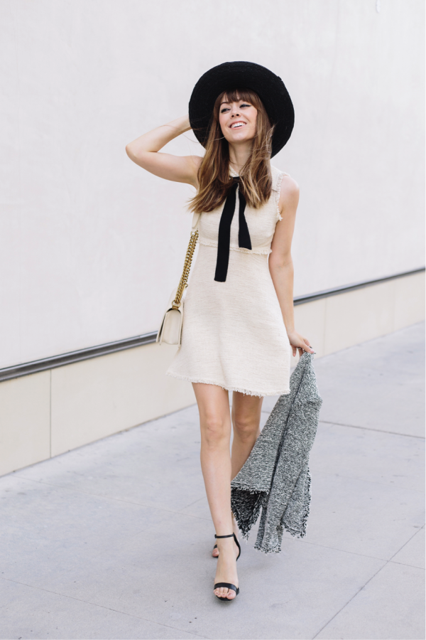 The frayed-edges of this Chanel-esque dress add a unique twist to this feminine look. Such a flattering style, and easily highly versatile, this is a look that could be worn all year round. Jenny Bernheim styles the fringed-dress with a black statement hat, black heels and a monochrome jacket. Dress: Zara, Hat: Nordstrom, Jacket: Shopbop