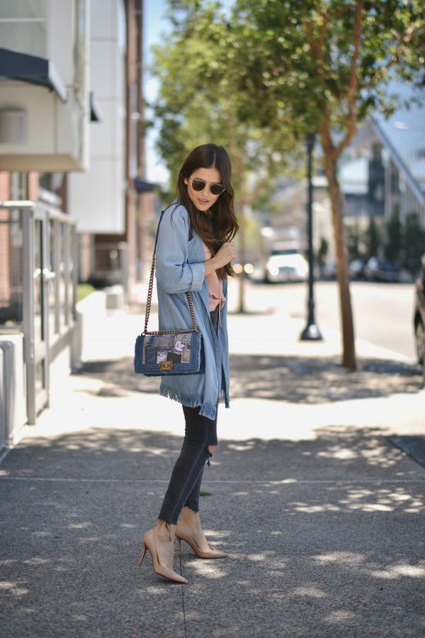 Paola Alberdi is casually elegant in a frayed edge oversize denim jacket, paired with distressed jeans and a pair of nude heels. This style is the perfect blend of edgy and swish; we love it! Jacket: BB Dakota, Top: Revolve, Jeans: Zara.