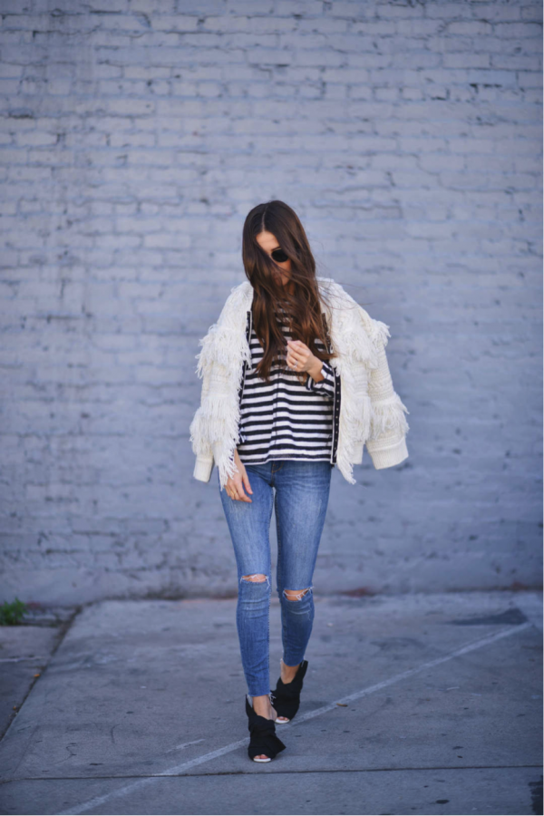 Paola Alberdi is spot on the frayed edges trend. The versatility of the white colour of the sweater results in a hugely versatile and iconic piece, which would embellish any outfit. The distressed jeans and striped shirt tone down the outfit, but nonetheless a sophisticated look is created. Sweater: saltwaterluxe, Top: Forever21, Jeans: Brand Not Specified