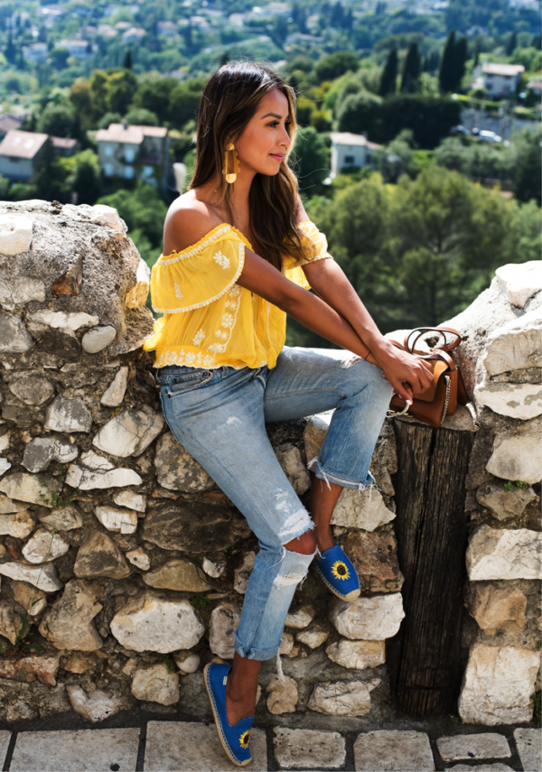 Add a bold, bright-coloured item to your wardrobe to really show your summer side. Julie Sarinana sports this vibrant and feminine yellow off-the-shoulder top, with some distressed jeans and lovely floral espadrilles. We adore this look! Espadrilles: Saludos, Jeans/Top: Brands not specified
