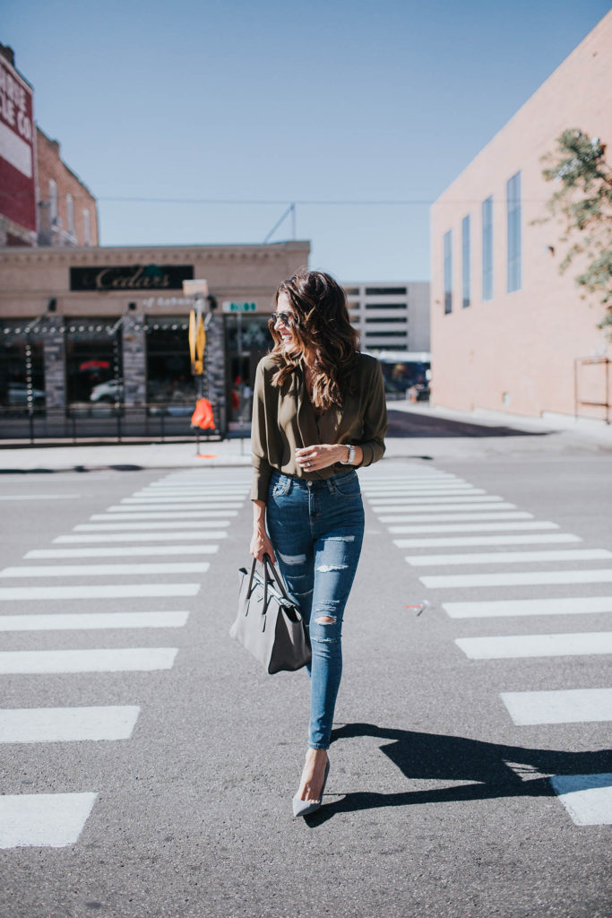 Distressed denim is a great way to add an edgy aspect to an outfit. Christine Andrew has chosen to pair her jeans with some gorgeous heels and a green summer blouse for an overall smart, and classic look.   Top: Nordstrom, Jeans: Topshop, Shoes: Manolo Blahnik