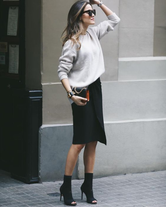 Alex Rivière is wearing an elegant black pencil skirt with a cream sweater and heeled open toe boots to create this spring style. Throw on a pair of shades to get this look! Bag: Sandro Paris.