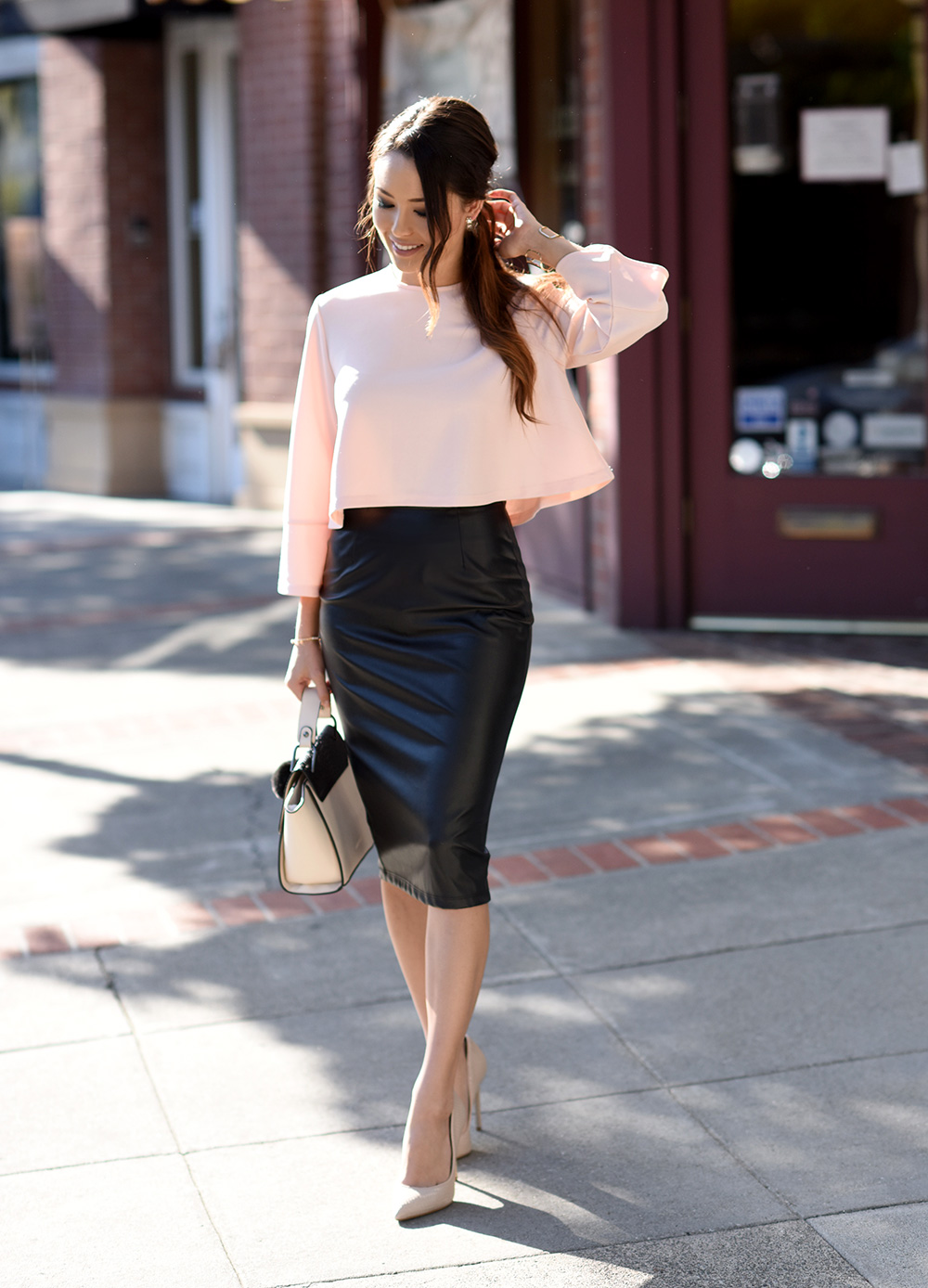 Jessica R. opts for a bold faux leather skirt paired with a girly pink top to create a fierce yet feminine style. Pair more punk (leather and jean) pencil skirts with florals, lace, or pastels to create eye-catching contrast. Skirt: Faux Leather, Top: West LA Boutique, Shoes: Steve Madden, Purse: Melie Bianco, Bracelet: Bebe, Earrings: Dainty and Bold