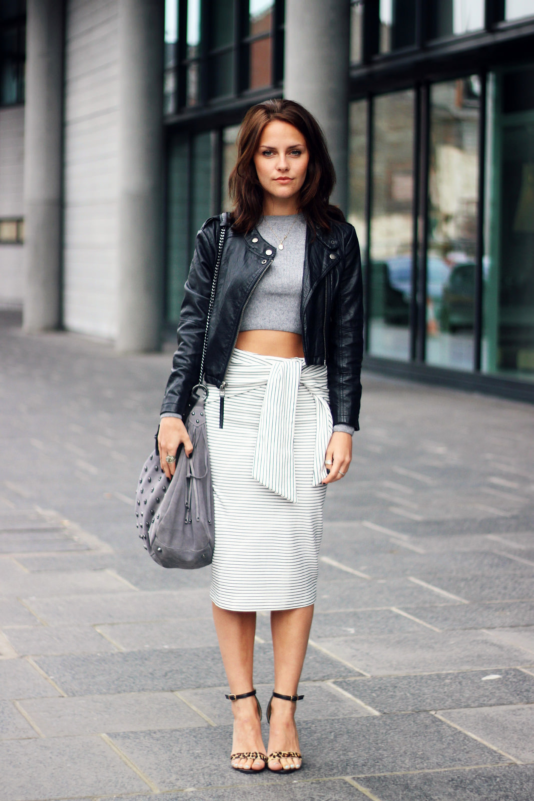 Amy Spencer is sporting one of our favorite modern, below-the-knee pencil skirts featuring pinstripes and a tie-waist. She pairs lighter neutrals (grey, white, and a chunky leopard print heel) together for a city-ready style, while showing off her tan with a cropped jumper. Skirt: Zara, Top: Topshop, Jacket: Topshop, Purse: Paul's Boutique, Shoes: Missguided