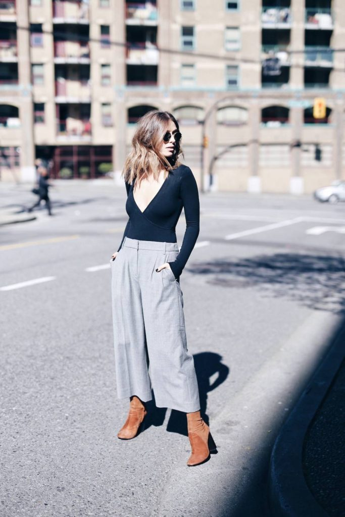 So chic, Jill Lansky shows how to wear a bodysuit with balance. Pairing a plunging neckline with classic grey culottes she teaches us how fit and flair works expertly with the bodysuit trend.   Bodysuit: American Apparel, Pants: J. Crew, Shoes: Zara, Sunglasses: Ray-Ban