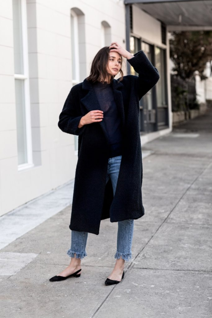 Elongated waists are a key fall 2016 trend. Sara Donaldson wears her long line black coat over a sheer sweater, quirky frayed jeans and another fall trend: slingback flats.  Coat: Christopher Esber, Jeans: 3×1, Top: THP