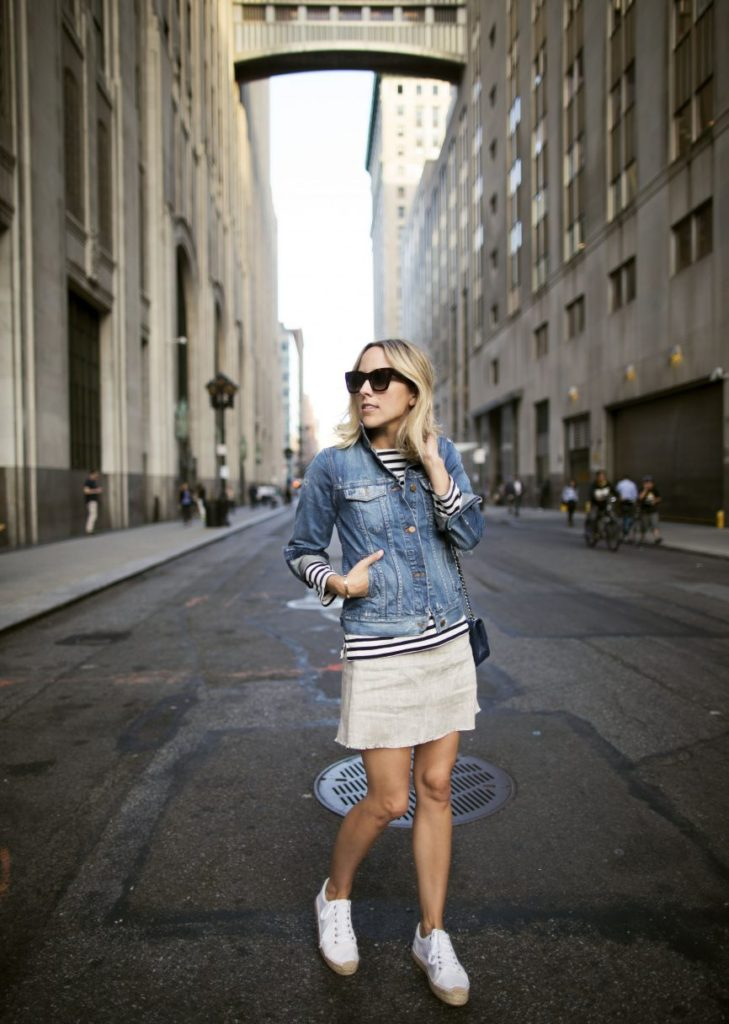 Stripes are everywhere this fall; Jacey Duprie wears her striped sweater under a denim jacket. This look is pretty versatile and can be worn with sandals, sneakers, and heels and in the fall, suede boots would also match perfectly. Jacket: Madewell, Sweater: J Crew, Skirt: Reformation, Shoes: Soludos, Bag: Chanel