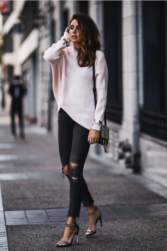 Erica Hoida adds a feminine blush pink sweater over her ripped denim jeans. Her embellished strappy sandals add a glamorous touch to her outfit. If you prefer block heels to stilettos then opt for patent ankle boots instead.  Sweater: Stella McCartney, Jeans: Rag and Bone, Shoes: Proenza Schouler, Bag: Chloe, Cuffs: Thpshp,