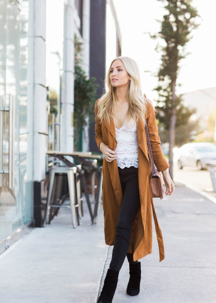 We are in awe of Sophie Elkus' gorgeously glam fall style, consisting of a sheer lace vest, black skinny jeans, and a classic duster coat. Wear this look with suede boots to capture this exact vibe!   Coat: Forever 21, Top: Nightcap, Jeans: Madewell, Boots: Stuart Weitzman.