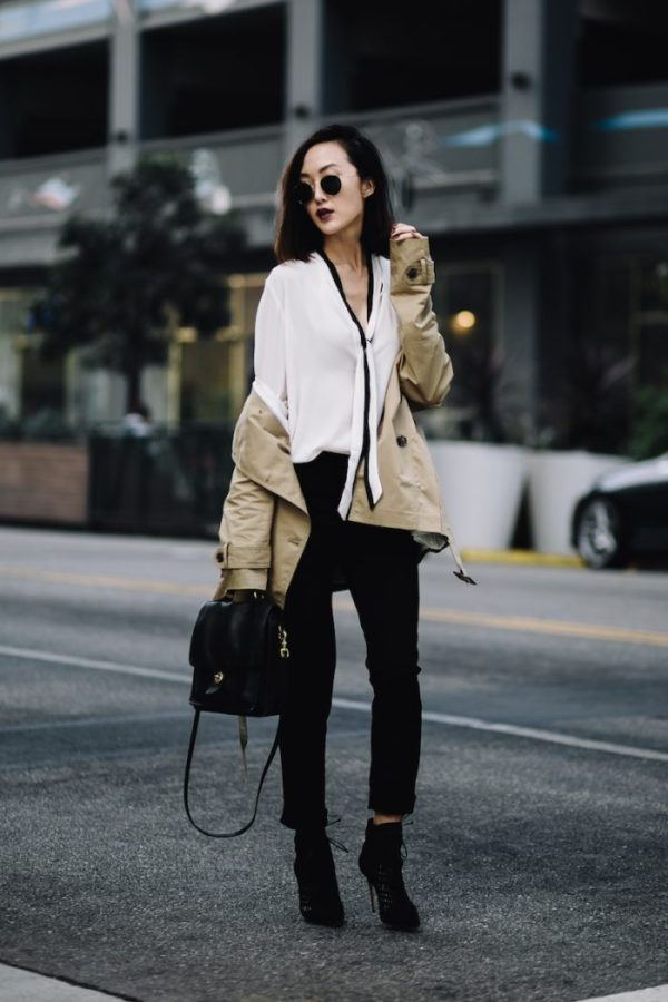 Chriselle Lim is glamorous and sexy in this sheer white blouse, worn with a classic beige overcoat and a pair of black cropped trousers. Wearing an outfit such as this with heeled boots will afford you Chriselle's simplistic glam. Trench/Blouse/Trousers: Banana Republic, Heels: Schultz, Bag: Vintage.