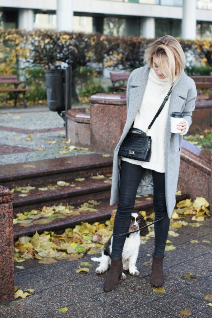 Katarzyna Tusk is casually glamorous in this outfit, consisting of skinny black jeans, a white knit sweater, and a sleek marl grey coat. Wear this look with suede boots to capture Katarzyna's vibe.   Sweater/Coat: MLE Collection, Jeans: Mango, Bag: Zara, Shoes: Massimo Dutti.