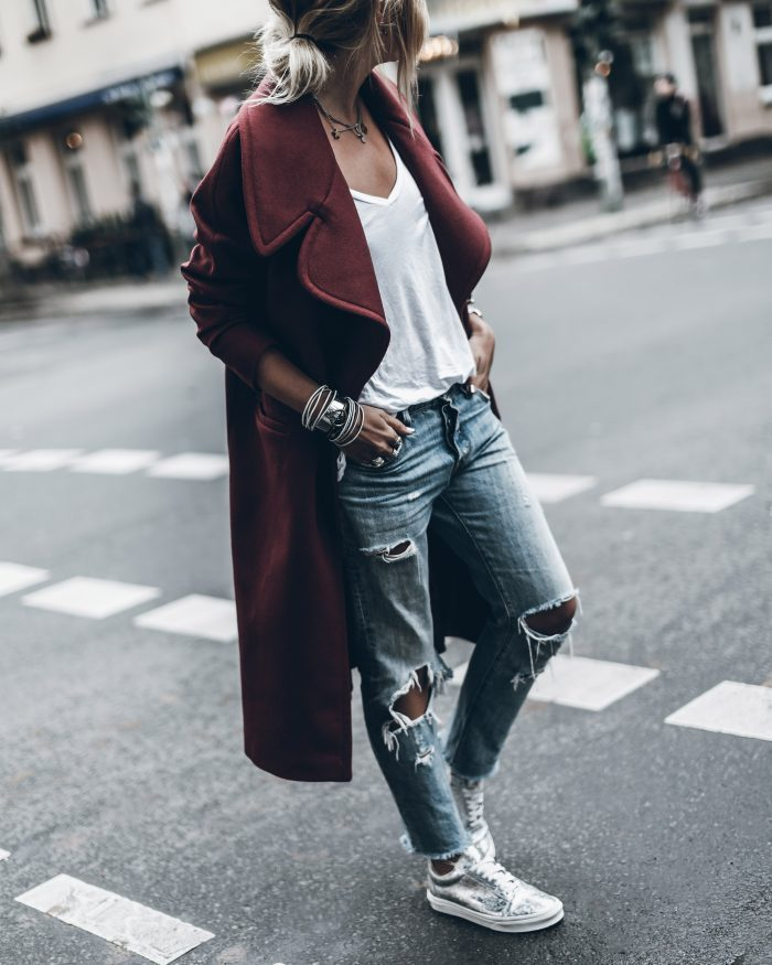 Distressed jeans are always a winner. By pairing this burgundy number with a white tee and distressed denim jeans, Jacqueline Mikuta has created a casual but edgy style which we love. Coat: Designers Remix, Shoes: Vans, Jeans: Levi's.