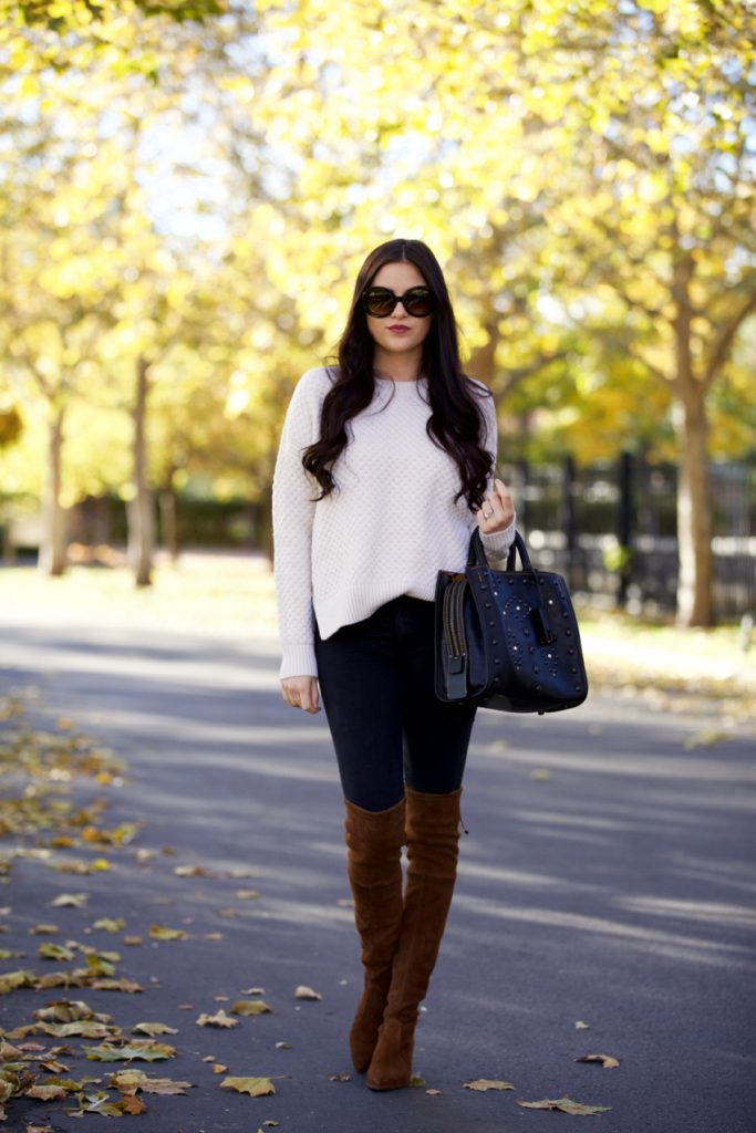 Rachel Parcell keeps it stripped back and authentic in this cosy fall style consisting of a knitted sweater, denim jeans, and a pair of gorgeous suede thigh high boots. Wear this look with minimal accessories to keep it simple and effective. Sweater: Vince, Jeans: Rag and Bone, Boots: Stuart Weitzman, Bag: Coach.