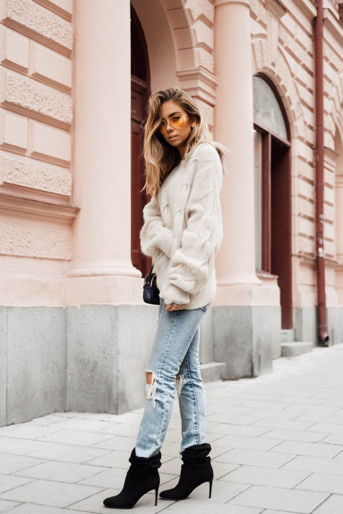 We are simply loving Lisa Olsson's glamorous yet casual street style consisting of an oversized chunky knit sweater, distressed acid wash jeans, and heeled booties. You have got to give this style a go this season! Sweater: & Other Stories, Jeans: Levi's.