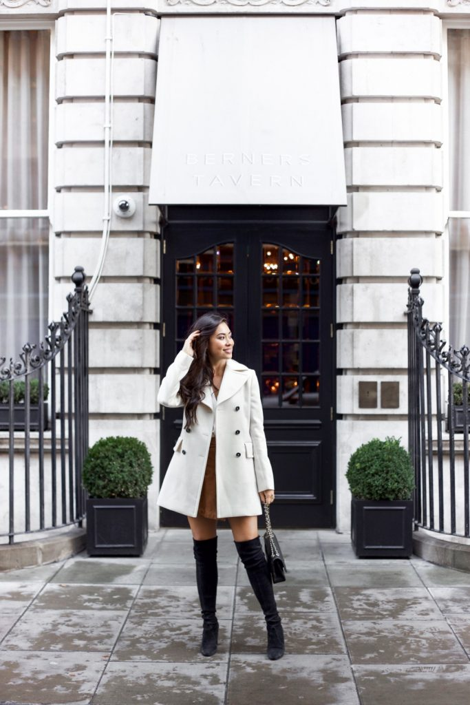 Kat Tanita is sleek and sexy in this fall outfit, consisting of a white coat, thigh high boots, and a mini dress. Try this look with a clutch bag and natural makeup to achieve these stripped back, glamorous vibes. Coat: Marni, Blouse: Theory, Skirt: Olivia Palermo, Boots: Stuart Weitzman.