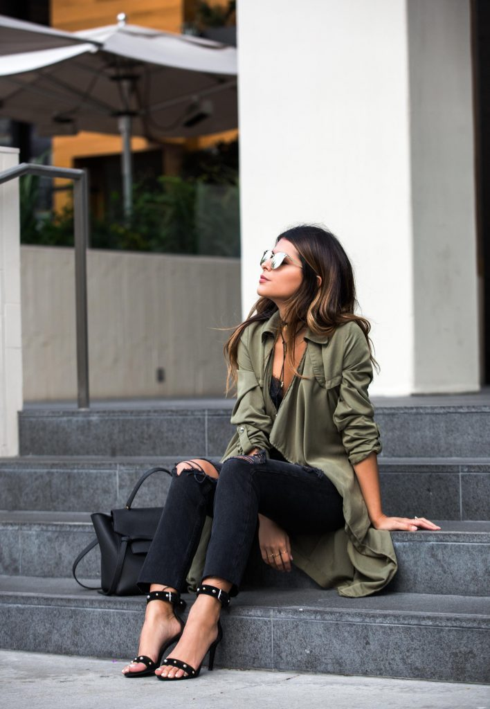 Pam Hetlinger is smart, elegant and feminine in this oversized silky shirt, paired with distressed black jeans and studded sandals for a chic finish! Throw on a pair of retro shades to capture the essence of this fall style. Jeans: Revolve, Top: Mango, Sandals: Maje, Coat: Duster, Bag: Celine.