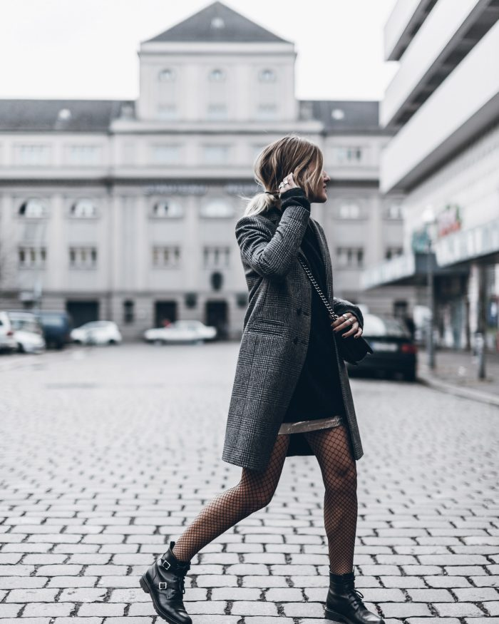 Jacqueline Mikuta is wearing an elegant yet casual fall style here, consisting of a tweed coat, fishnet tights, and a pair of buckled leather boots. A style like this is ideal for those everyday fall mornings. Coat: Sezanne, Sweater/Skirt/Tights: H&M, Boots: Saint Laurent.