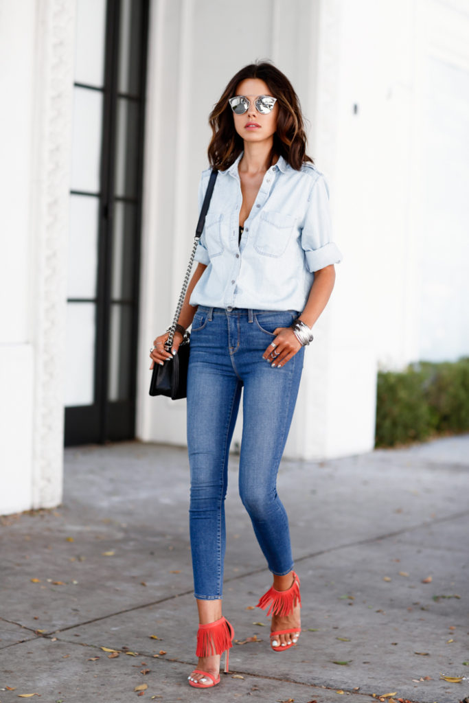 Annabelle Fleur doubles a light denim shirt with a pair of mid-blue high waisted denims. Her orange fringed sandals bring a modern and sexy twist to this outfit.  Margot high-rise skinny jeans: L'Agence, Lovefringe suede sandals: Stuart Weitzman, Medium wash denim boyfriend shirt: Express, Boy flap bag in perforated leather: Chanel, So Real 48mm sunglasses: Dior multi tube bracelets: Gillian Julius