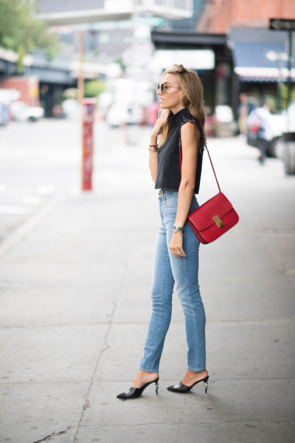 "Lisa D Cahue pairs a cropped top that cuts off at her midriff exposing the high waist of her jeans to accentuate the length of her legs. This denim-on-denim outfit is finished with a gorgeous black mule that lengthens the foot. Add to this the small red satchel and amber sunglasses, and you have one smoking hot look. Top: Rachel Comey, Jeans: Khaite, Shoes: Chanel, Bag: Celine, Sunglasses: Ahlem ""concorde,"" Bracelets: Vita Fede and Miansai"