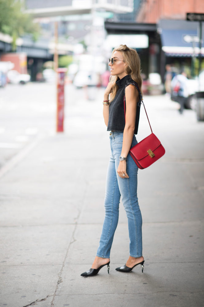 """Lisa D Cahue pairs a cropped top that cuts off at her midriff exposing the high waist of her jeans to accentuate the length of her legs. This denim-on-denim outfit is finished with a gorgeous black mule that lengthens the foot. Add to this the small red satchel and amber sunglasses, and you have one smoking hot look. Top: Rachel Comey, Jeans: Khaite, Shoes: Chanel, Bag: Celine, Sunglasses: Ahlem """"concorde,"""" Bracelets: Vita Fede and Miansai"""