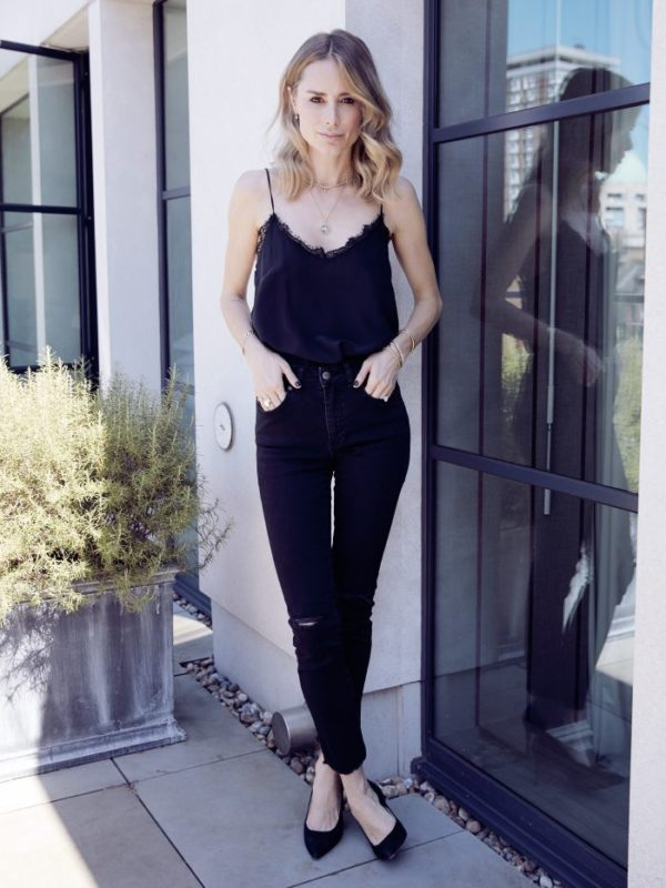 Anine Bing marries two elements from the 90s in a contemporary way. The silk camisole tucked into her high waisted black jeans creates a chic look. Simple ballerinas in pony, and gold accessories, adds contrast and texture to this black on black look. Silk Camisole in Black, High Waisted Ripped Jeans in Black Collette Ballerinas in Pony Hair all by Annie Bing
