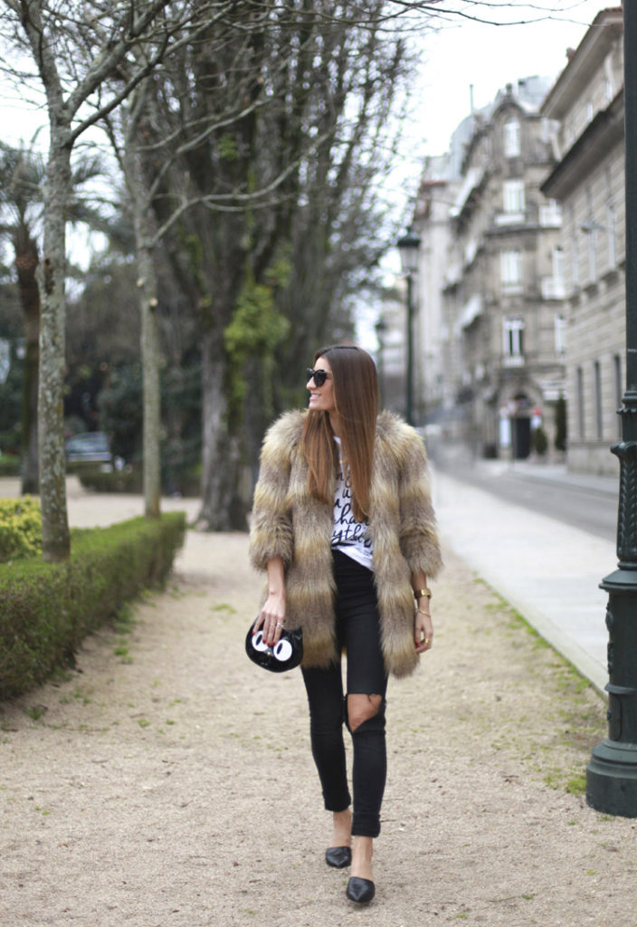 Silvia Garcia mixes it up when her ripped jeans meet the glam of her fur coat. This sophisticated yet playful look is uber cool. The black jeans sync with the printed words of the T-shirt and her simple black flats. Completing the look Garcia adds the ultimate accessory – a cat clutch!  T-Shirt: À Bicyclette, Faux fur coat: bought in London years ago, Jeans: Stradivarius, Shoes: Laboratorio 917, Bag: Suiteblanco, Necklace: By Neska Polita Watch: Nixon