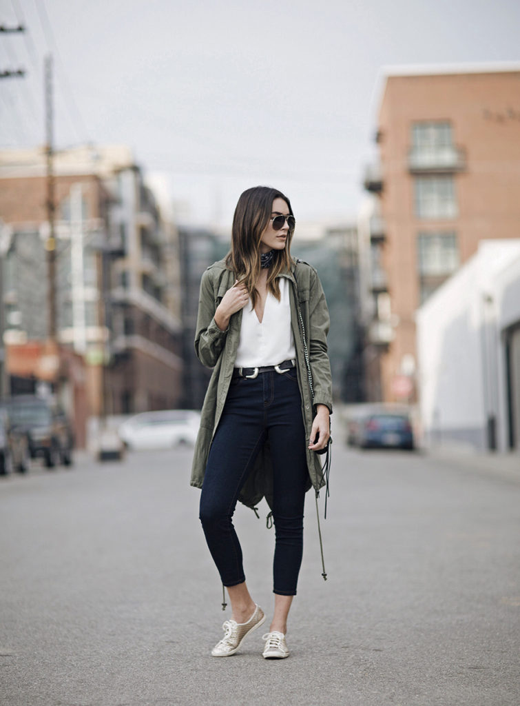 Brittany Xavier adds layers to this outfit with an oversized Khaki anorak that covers a soft, low necked shirt tucked into a high waisted jean. Her gold Keds provide a causal elegance complimented with the ultimate in cool – a pair of aviators. The double buckled belt is a hot ticket item this season.  Jacket: Forever 21 Jeans: Forever 21, Sneakers: Keds Belt: ASOS Bag: Rebecca Minkoff, Sunglasses: Valentino