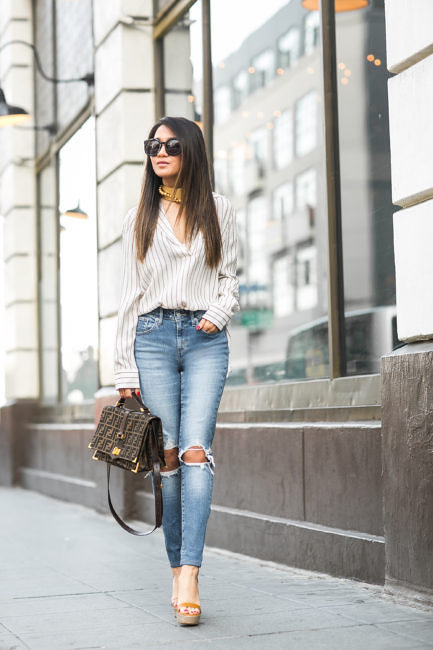 Wendy Nguyen accentuates the length of her legs in these high waisted form-fitting jeans. The ripped, distressed and high waisted jean spells out causal yet comfortable. She finishes this outfit with a soft pin-striped shirt. The platform sandals, Fendi bag and oversized sunglasses personalise her chic street-wear look. Shirt: Frame, Jeans: Levi's, Bag: Fendi, Shoes: M.Gemi, Sunglasses: Karen Walker, Watch: Daniel Wellington