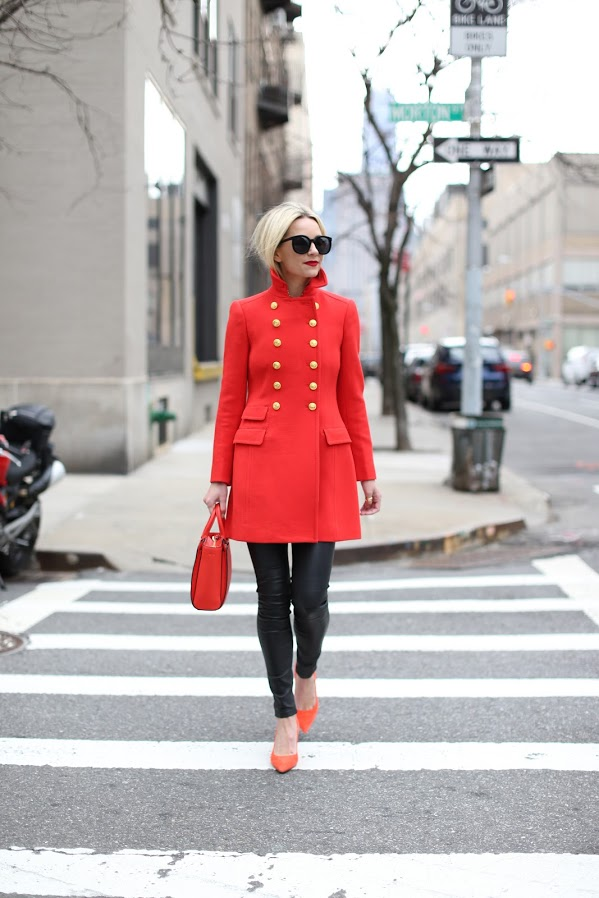 """Blair Eadie zhooshes up the traditional military jacket in a hit of poppy red. She add black leather trousers under this long jacket and finishes the look with coordinated accessories and shoes. Her bob cut and oversized sunnies further """"chic"""" this look up.  Jacket: model's own collection. purse: Tony Birch """"Robinson Tote"""", Pumps: Tony Burch, Pants: Current/Elliot, Sunglasses: Karen Walker"""