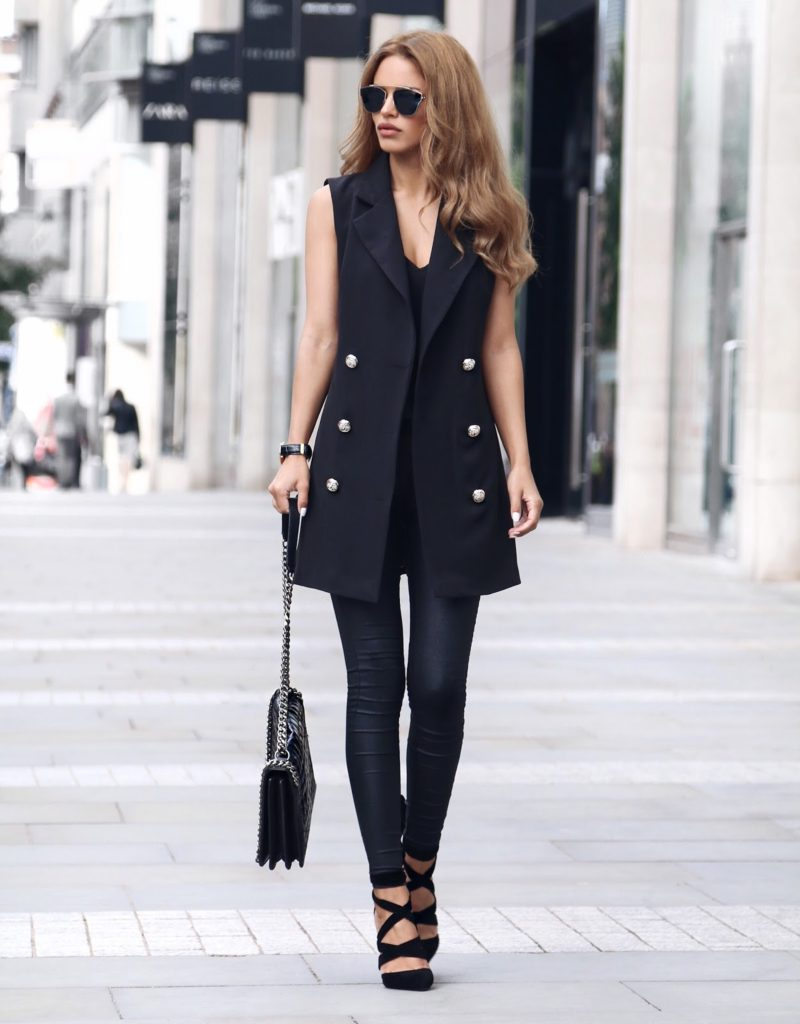 This sleeveless blazer softens the military jacket staple this season. Teamed with a pair of black leather pants, and a gorgeous pair of strappy heels, Nada Adellè adds femininity and sophistication to this outfit. The silver rounded buttons and the bag chain add accents to this all black outfit.  Sleeveless Blazer: Boohoo, Cami Top: Forever 21, Leather Pants: Asos, Blake Heels: Public Desire, Croc Chain Bag: Zara, Sunglasses: La Moda