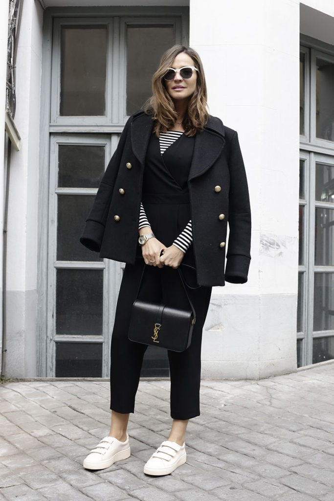 Silvia Zamora marries the classical nautical stripe with the military pea coat. Accessorised with strapped trainers and that gorgeous YSL bag, this is one seriously chic look for Fall.  Coat: Balmain, Jumpsuit: Topshop, Striped T-shirt: Lovers and Friends, Sneakers: Sandro, Sunglasses: Max Mara, watch: Marc Jacobs, Bag: YSL