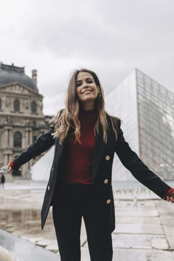 Sara Escudero's simple military-inspired jacket, with its large flat buttons, is worn over a red turtleneck and black pants. She wears burgundy sandals, but try adding black ankle boots to keep dry in the winter. Blazer: Reiss, Top: ASOS, Sandals: Reiss, Earrings: Topshop