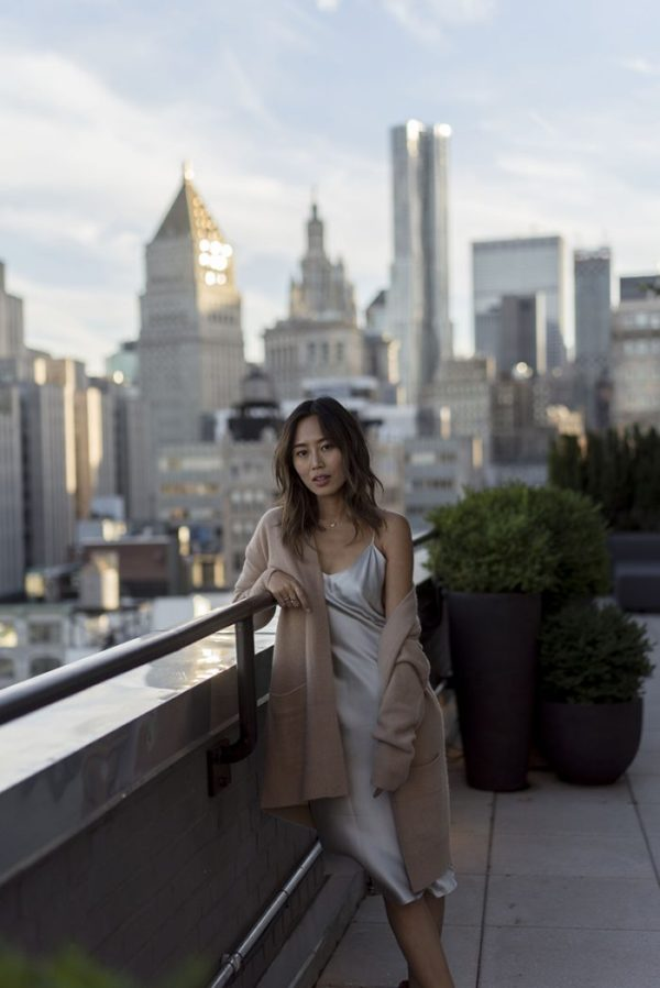Aimee Song is breathtaking in this gorgeous slip dress by Nili Lotan, worn with a cardigan and minimal jewellery for a stripped back, natural look. Keep your colour scheme neutral to recreate this elegant style. Dress: Nili Lotan, Cardigan: Vince, Boots: Celine.
