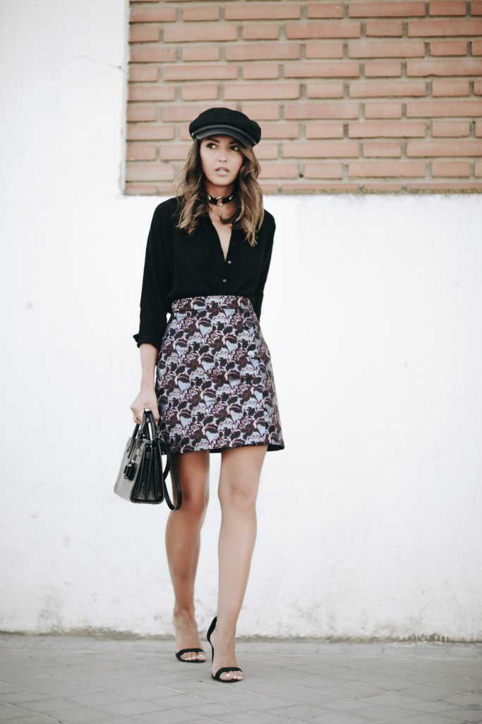 Alexandra Pereira is oh so sophisticated and feminine in a floral skirt, black blouse and nude lip. We are absolutely loving her retro newsboy cap and choker with metal accents.   Skirt: Farfetch, Shirt: Zara, Sandals: Shutz, Bag: YSL, Hat and Choker: Asos