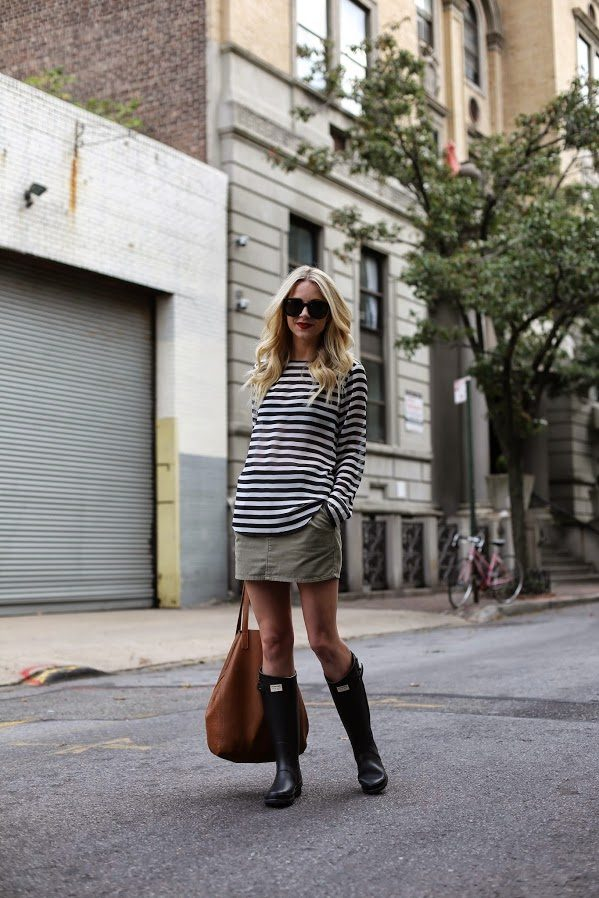 City style ready Blair Eadie looks cooler than cool after pairing her Hunter Boots with an olive corduroy skirt. The unstructured tan tote keeps the whole look perfectly casual. Top: Ann Taylor, Skirt: Denim and Supply, Bag: Cuyana Tall tote, Boots: Hunter, Sunglasses: Karen Walker