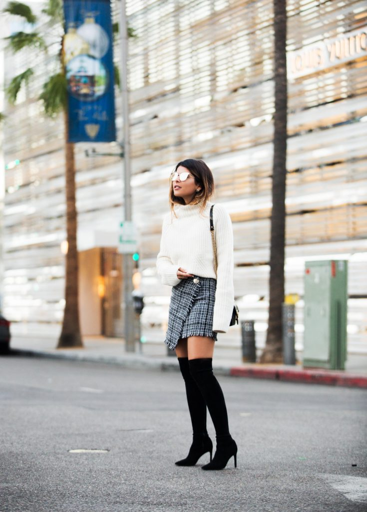 This really is a foolproof way to style a tweed skirt! Pam Hetlinger looks totally cute in this winter style consisting of a white knitted sweater and a wrap around tweed skirt, brought together with a pair of striking over the knee boots and some shades. We absolutely adore this simple style.   Skirt: Storets, Sweater: LPA via Revolve, Boots: Delman, Bag: Gucci.