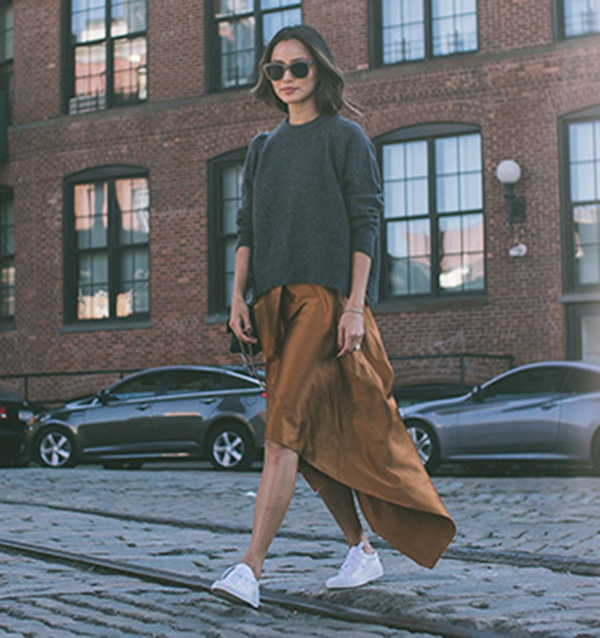 Silky bronze has never looked so effortless than with classic white sneakers and a baggy charcoal sweater. Via Jamie J Chung.  Skirt and Sweater: Elizabeth and James, Shoes: Barneys, Sunglasses: Shopbop