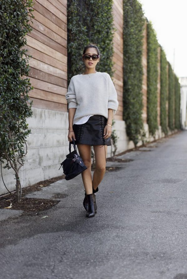 Mastering L.A. street style, Aimee Song plays hard and soft in a laced leather skirt and oversized boatneck sweater. Sweater: Nili Lotan sweater, Boots: Kenzo, Bag: Rag + Bone, Sunglasses: Celine