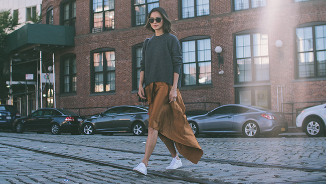 Silky bronze has never looked so effortless than with classic white sneakers and a baggy charcoal sweater. Via Jamie J Chung  Skirt and Sweater: Elizabeth and James, Shoes: Barneys, Sunglasses: Shopbop